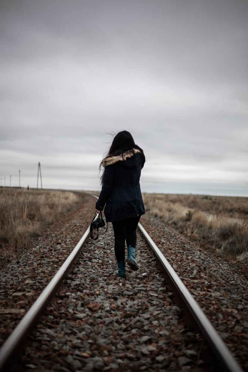 woman walking in middle of railway